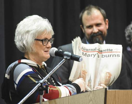Cathy Stoffel, who taught eighth-grade English at Summit  when it opened in 1993, holds up a copy of The Journal Gazette that was in a time capsule  opened Thursday.