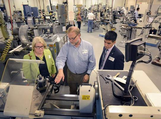 FILE: Meg Distler of the St. Joseph Community Health Foundation, left, Bob Distler of Superior Essex and Jorge Ortiz of Sen. Donnelly's office tour the advanced manufacturing lab at Ivy Tech, which was touting its new CNC Machining Operator Program.
