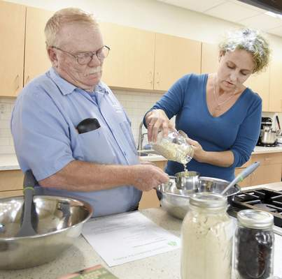 Rachel Von | The Journal Gazette Kelley Marvin helps Tim Gumns pour oats during a cooking demonstration for Easterseals Arc Northeast Indiana staff this summer at the Jackson R. Lehman Family YMCA.