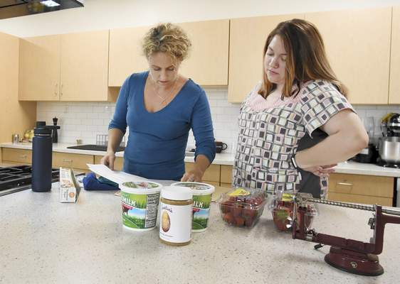 Rachel Von | The Journal Gazette  Kelley Marvin, left, and Megan Herrmann, RN with Easter Seals, looks over the recipes during Marvin's cooking demonstration for adults from Easter Seals at Jackson R. Lehman Family YMCA on Wednesday July 25, 2018.