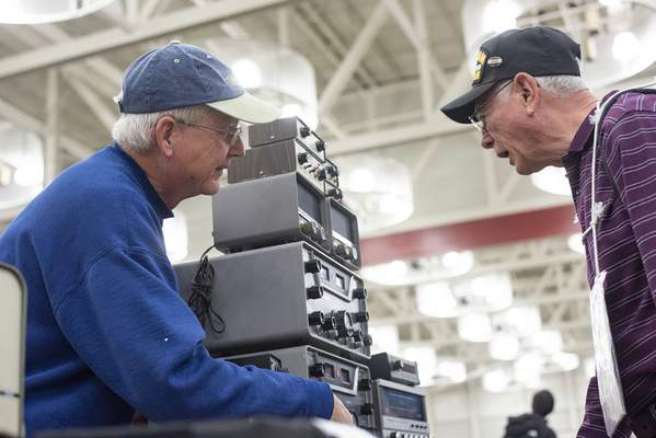 Brett Luke | The Journal Gazette  Tracy Michael shows various vintage radios, transceivers, transmitters and other electronics to John Dyrek Saturday morning at the Hamfest and Electronics Expo held at Memorial Coliseum.