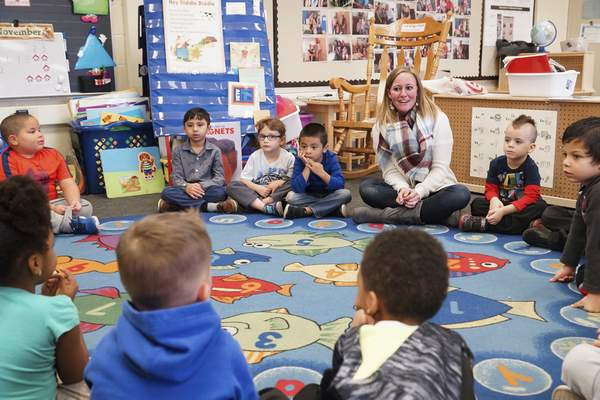 Mike Moore | The Journal Gazette  Lacey Metzger, pre-K teacher at Franke Park Elementary School, works with her students Monday. Metzger believes attending pre-K prepares children for elementary school.