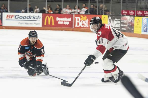 Brett Luke | The Journal Gazette Ryan Lowney, of the Komets, chips the puck past Cincinnati's Dominic Zombo during the first period at the Memorial Coliseum Saturday night.