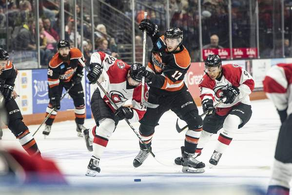 Brett Luke | The Journal Gazette Justin Kea of the Komets intercepts and passes the puck before being sandwiched by Cincinnati during the second period at the Memorial Coliseum Saturday night.