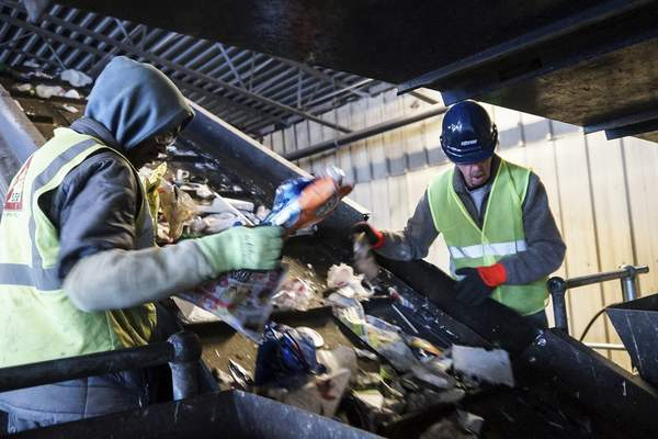 Mike Moore | The Journal Gazette  Employees of Republic Services sort out paper products at the company's East Pontiac Street recycling facility in Fort Wayne.