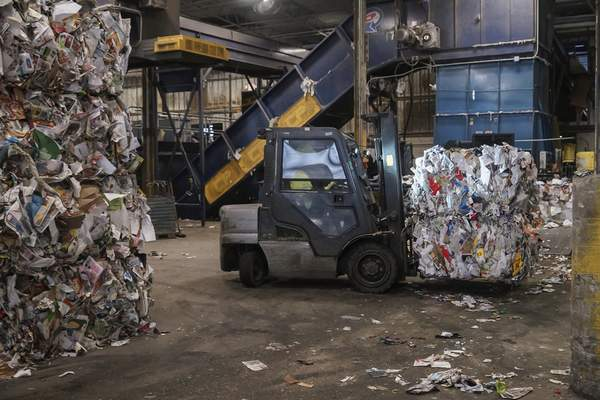 Mike Moore | The Journal Gazette  Bales of paper products are moved to a storage facility with a forklift before being recycled at the Republic Services recycling facility on East Pontiac Street in Fort Wayne.