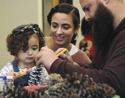 Luisa and Juan Villa make a pine cone ornament with their 2-year-old daughter, Mikaela, Saturday at the Allen County Public Library downtown.