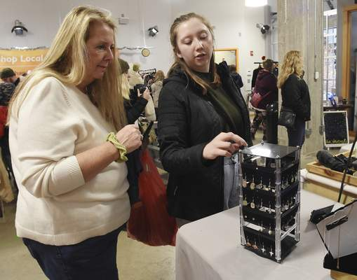 Rachel Von   The Journal Gazette  Peggy Gaskill, left, and daughter Ellie look at earrings at the Jewelry by Matt Breunig booth in the City Exhange Shops during the Holly Trolley Shopping event on Saturday.