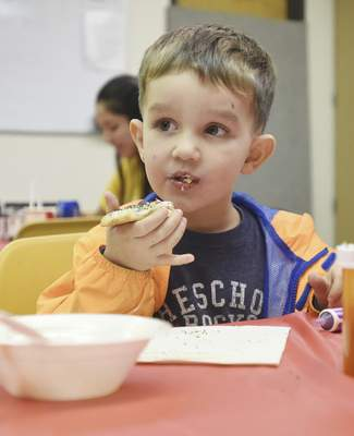 Rachel Von   The Journal Gazette  Avery Goeglein, 3, enjoys a big bite of a Christmas cookie at a decorating event held at the Community Center on Main Street during the Holly Trolley Shopping event on Saturday.