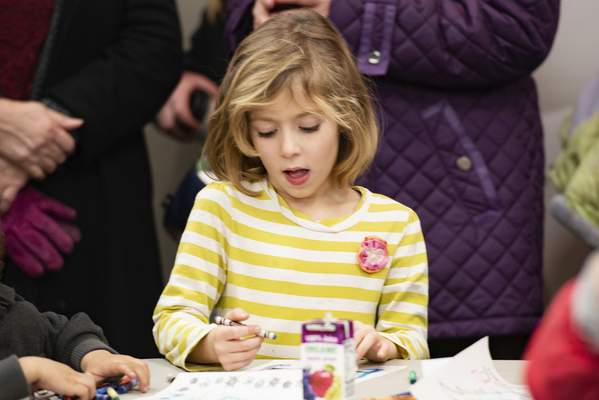 Jazmyn Scott, 5, takes a break from the lights to color during the festivities.
