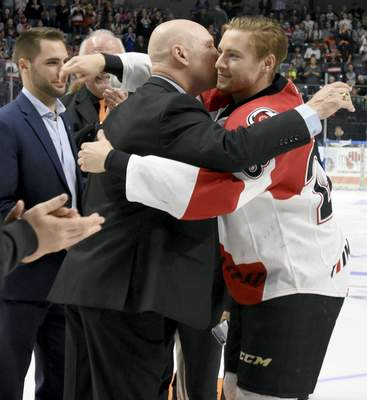Rachel Von   The Journal Gazette  Jordan Sims, right, hugs his father, Al, before the latter's jersey retirement ceremony at Memorial Coliseum in 2017. Jordan Sims will now be a member of the Komets, the team his father played for and coached to five championships.