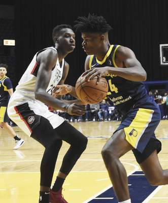 Rachel Von | The Journal Gazette  Mad Ants' Alize Johnson pushes past Raptors 905's Chris Boucher to get to the hoop during the first half at the Coliseum on Thursday.