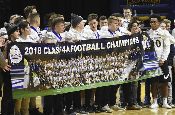 Rachel Von   The Journal Gazette Bishop Dwenger football players accept a banner during a presentation during the Mad Ants vs. 905 Raptors game at the Memorial Coliseum on Thursday celebrating their 2018 Class 4A football championship win against Evansville Central.