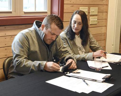 Lisa Anne Schrader, with Reecer Properties Inc., watches as Travis Platt writes a check for the Dick Freeland horse farm, which he and partner Robert Andrews bought at auction Thursday.
