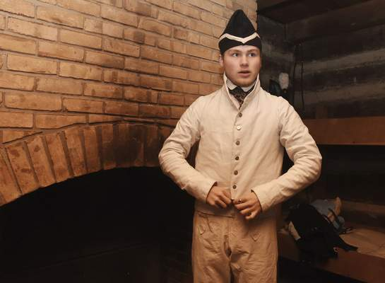 Harrison Snyder changes into his different period clothing inside the barracks at the Old Fort. A program at the Old Fort has several period soldiers on the grounds drilling, cooking and occupying the fort as it would have been in 1816.