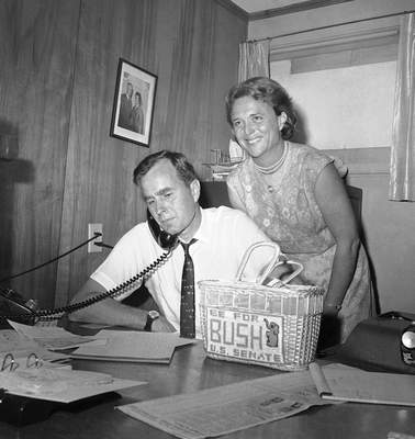 FILE - In this June 6, 1964, file photo George H.W. Bush, candidate for the Republican nomination for the U.S. Senate, gets returns by phone at his headquarters in Houston, as his wife Barbara, smiles at the news. (AP Photo/Ed Kolenovsky, File)