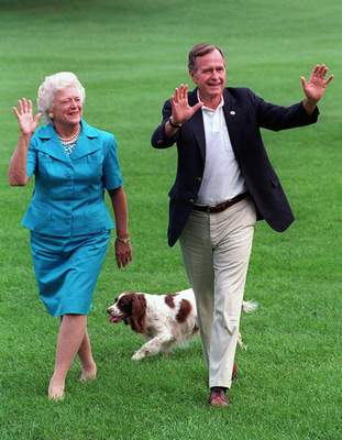 FILE - In this Aug. 24, 1992, file photo, President George H.W. Bush and first lady Barbara Bush walk with their dog Millie across the South Lawn as they return to the White House. Bush has died at age 94. (AP Photo/Scott Applewhite, File)