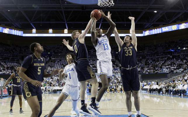 UCLA guard Kris Wilkes (13) drives to the basket between Notre Dame's Rex Pflueger (0) and John Mooney (33) during the first half of an NCAA college basketball game Saturday, Dec. 8, 2018, in Los Angeles. (AP Photo/Marcio Jose Sanchez)