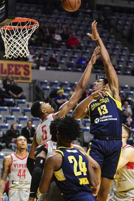 Mike Moore | The Journal Gazette Mad Ants center Ike Anigbogu takes a shot at the basket guarded by Rio Grande Valley forward Bruno Caboclo in the first quarter at Memorial Coliseum on Monday.