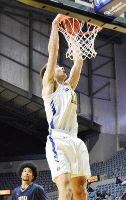 Elizabeth Wyman | Journal Gazette  Dylan Carl finishes a dunk in Thursday night's game against Siena Heights at Memorial Coliseum. The Mastodons finish their nonconference schedule with an 8-7 record.