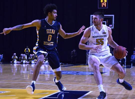 Elizabeth Wyman | the Journal Gazette  John Konchar drives against Siena Heights' DeMarco Dickerson on Thursday night at Memorial Coliseum. Konchar finished with 20 points and 10 rebounds.
