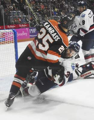 Rachel Von   The Journal Gazette  The Komets' Jake Kamrass takes down the Wings' Luke Sandler during the first period at the Coliseum on Thursday.