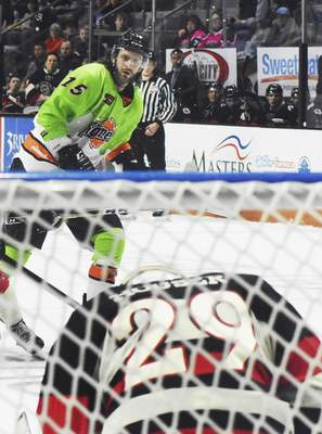 Rachel Von | The Journal Gazette  Komets' J.C. Campagna shoots the puck at Cyclones goalie Michael Houser during the second period at the Coliseum on Saturday.