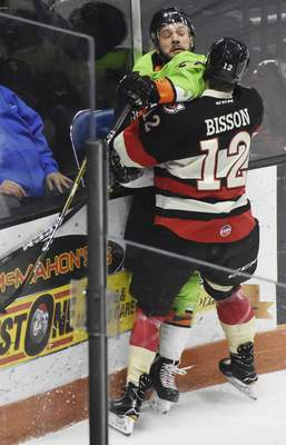 Rachel Von | The Journal Gazette  Komets' Shawn Szydlowski gets checked by the Cyclones' Tobie Bisson during the first period at the Coliseum on Saturday.