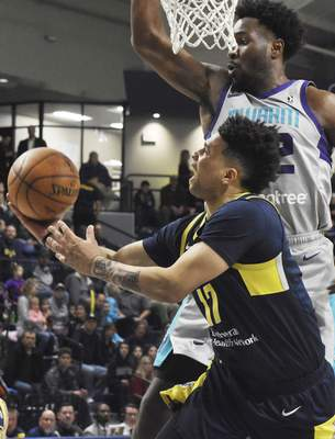 Rachel Von | The Journal Gazette  Mad Ants' Stephan Hicks jumps up to shoot the ball as Swarm's Chinanu Onuaku tries to block his shot during the second quarter in the MTI Center at Trine on Sunday.
