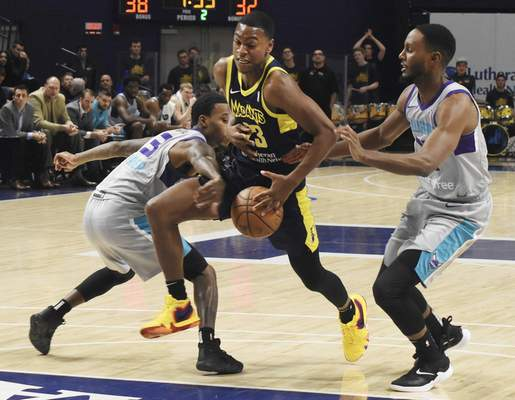 Rachel Von | The Journal Gazette  Mad Ants' Demetrius Denzel-Dyson tries to keep ahold of the ball as Swarm's Cat Barber, left, and Sam Thompson try to knock the ball from his grip during the second quarter in the MTI Center at Trine on Sunday.