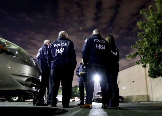FILE - In this Jan. 10, 2018, file photo, U.S. Immigration and Customs Enforcement agents gather before serving an employment audit notice at a 7-Eleven convenience store, in Los Angeles. (AP Photo/Chris Carlson, File)