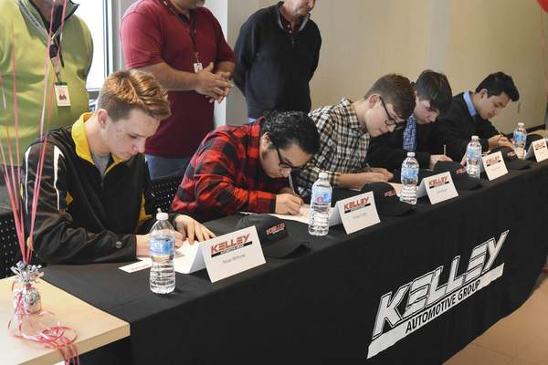 FWCS Career Academy students, from left, Nolan McKuras, Enrique Trujillo, Jacob Maggart, Keagan Snaufer and Jose Cortez sign on to become paid service technician interns at Kelley dealerships. (Michelle Davies | The Journal Gazette)
