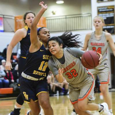 Mike Moore | The Journal Gazette  Indiana Tech guard Bella Lozano-Dobbs drives to the basket guarded by Siena Heights guard Anaya Powell in the second quarter at the Schaefer Center on Wednesday.