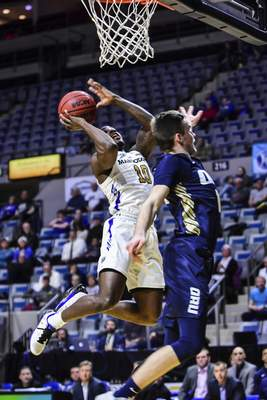 Mike Moore | The Journal Gazette Purdue Fort Wayne guard Dee Montgomery scores over Oral Roberts guard Carlos Jurgens in the first half Thursday night at Memorial Coliseum.