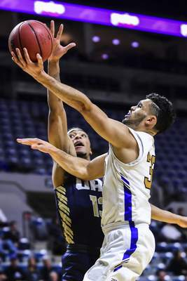 Mike Moore | The Journal Gazette Purdue Fort Wayne guard Kason Harrell drives to the basket over Oral Roberts guard Aidan Saunders in the first half at Memorial Coliseum on Thursday.