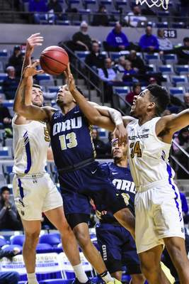 Mike Moore | The Journal Gazette  Purdue Fort Wayne defenders John Konchar, left, and Cameron Benford, right, fight for a rebound with Oral Roberts guard Aidan Saunders, center in the first half at Memorial Coliseum on Thursday.