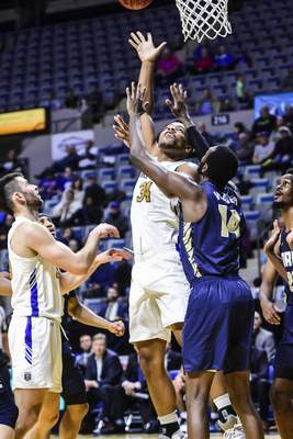 Mike Moore | The Journal Gazette Purdue Fort Wayne forward Cameron Benford scores under the basket over Oral Roberts forward Deshang Weaver in the first half at Memorial Coliseum on Thursday.