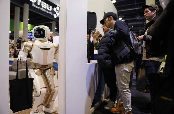 Associated Press photos The Walker robot stands in a doorway during a demonstration at the Ubtech booth at CES International on Wednesday in Las Vegas.