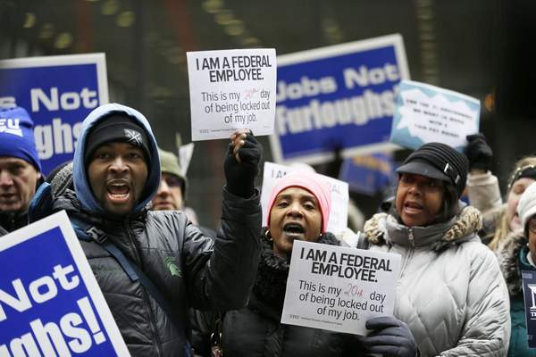 Government workers rally against the partial government shutdown at Federal Plaza, Thursday, Jan. 10, 2019, in Chicago. (AP Photo/Kiichiro Sato)