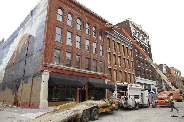 Mike Moore   The Journal Gazette Construction crews work high above West Columbia Street on Friday using an aerial work platform.