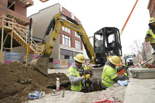Mike Moore   The Journal Gazette Work crews from NIPSCO work on a gas main below West Columbia Street on Friday.