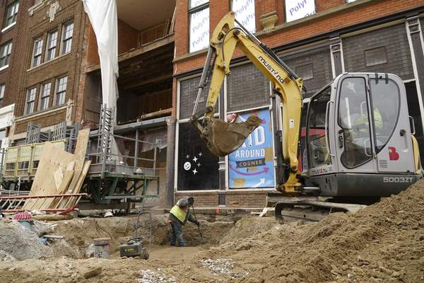 Mike Moore   The Journal Gazette Construction crews work on a building foundation on West Columbia Street on Friday.