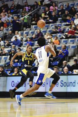 Katie Fyfe | The Journal Gazette  The Mad Ants' Je'Lon Hornbeak and the Magic's Braian Angola chase after the ball during the second quarter at the Coliseum on Saturday.