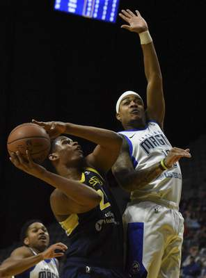 Rachel Von | The Journal Gazette  The Mad Ants' Jared Sam tries to shoot the ball as the Magic's Troy Caupain tries to block his shot during the second quarter at the Coliseum on Saturday.