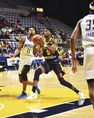 Katie Fyfe | The Journal Gazette  The Mad Ants' Edmond Sumner shoots the ball while Magic's Braian Angola tries to block his shot during the first quarter at the Coliseum on Saturday.