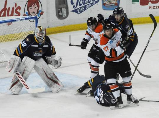 Justin A. Cohn   The Journal Gazette  Komets forwards Shawn Szydlowski, right, and Anthony Petruzzelli, middle, battle with the Toledo Walleye's Zach Urban, on the ice, and Justin Kea, as goalie Pat Nagle looks on Sunday at the Huntington Center.