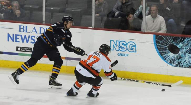 Justin A. Cohn   The Journal Gazette  The Komets' Matthew Weis, right, defends as the Toledo Walleye's Samuel Thibault sends the puck up the Huntington Center boards Sunday.
