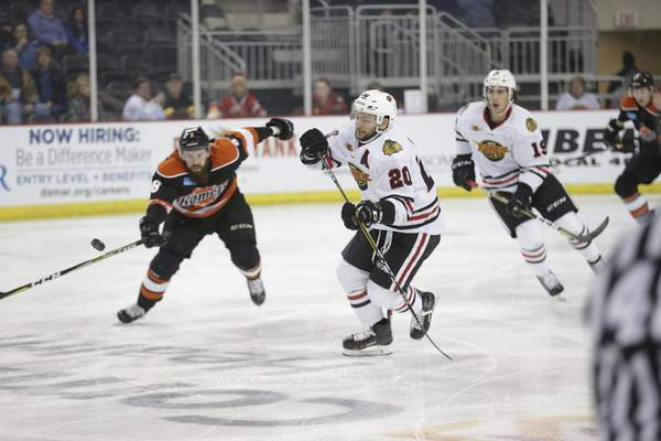 Whiteshark Photography  Komets forward Taylor Crunk, left, and the Indy Fuel's Matt Rupert, right, chase the puck Friday at Indiana Farmers Coliseum in Indianapolis.