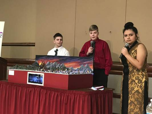 Jamie Duffy| The Journal Gazette  Kekionga middle school students, from left, Jude Ratajczak, David Norman and Gaby Gonzalez present the school project in front of a panel of judges at the 2019 Indiana Future City Competition. The project came in fifth overall.