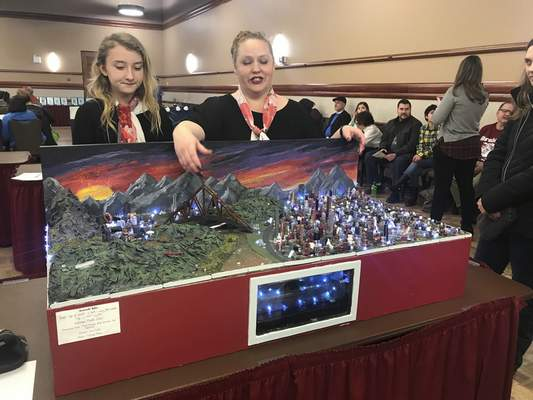 Jamie Duffy | The Journal Gazette  Kekionga middle school student Makaylee Born, left, and Kate Curless, adviser and math teacher at Kekionga, look over the school's project at the 2019 Indiana Future City Competition Saturday at Purdue University Fort Wayne. The school's project came in fifth overall and took home two best awards.